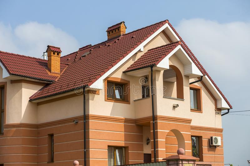 Stora moderna dyra lyxiga bostads- två-berättelser stuga, familjhus med det överlappade bruna taket, höga tegelstenlampglas, stuc royaltyfria bilder