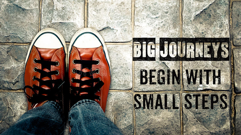 Stora resor börjar med små moment, inspirationcitationstecken arkivfoton