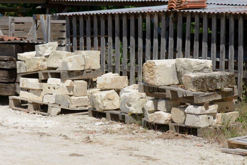 Stora stenar som staplas i högar för att vara van vid byggandehus fotografering för bildbyråer