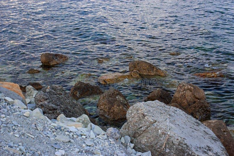 Stora stenar vid havet på en lös strand med kiselstenar royaltyfria foton