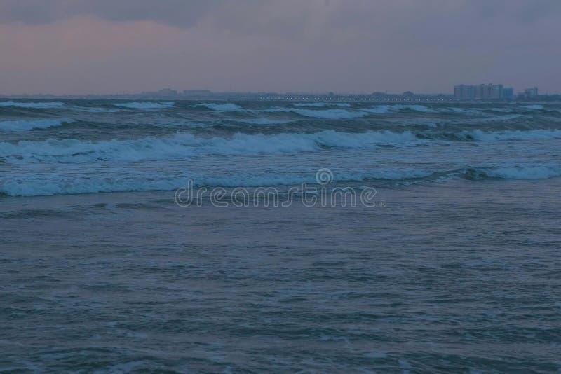 Stora stormskumvågor i havet på solnedgången i den mörka aftonen i mörkret Kuststad på bakgrund royaltyfri foto