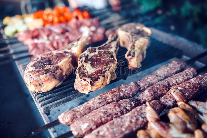 Stora stycken av inlagt kött på ett raster i en restaurang Blandade grillade k?tt arkivbild