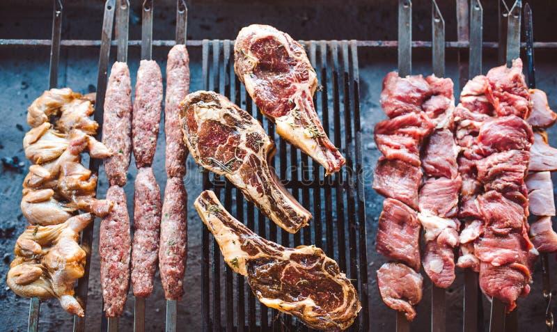 Stora stycken av inlagt kött på ett raster i en restaurang Blandade grillade k?tt royaltyfri bild