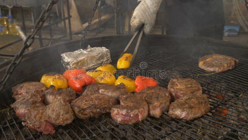 Stora stycken av kött och peppar på gallret, avslutningen av matlagning, kocken tar det färdiga köttet med järn royaltyfria bilder