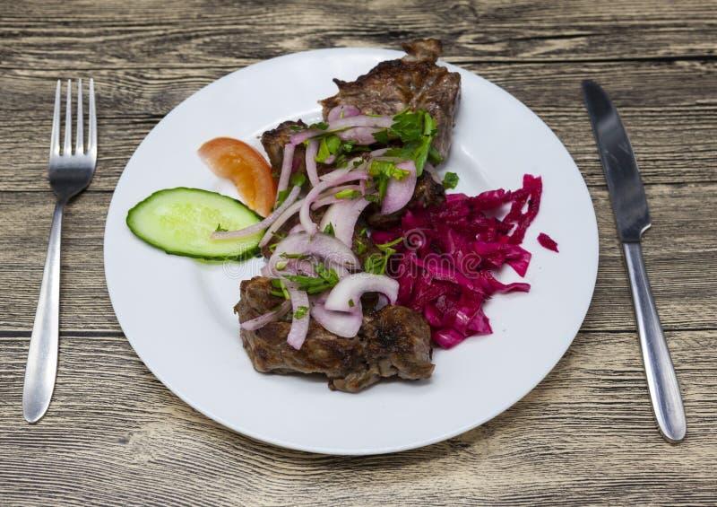 Stora stycken av stekt griskött som garneras med nya veggies på plattan Steknålar av stora stycken av griskött med en garnering a royaltyfri fotografi