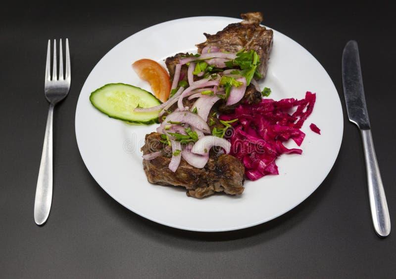 Stora stycken av stekt griskött som garneras med nya veggies på plattan Steknålar av stora stycken av griskött med en garnering a arkivfoto