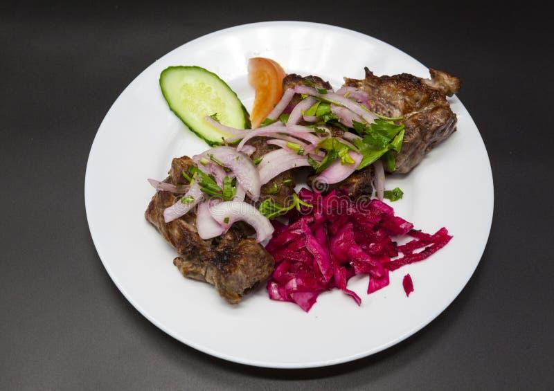 Stora stycken av stekt griskött som garneras med nya veggies på plattan Steknålar av stora stycken av griskött med en garnering a arkivfoton