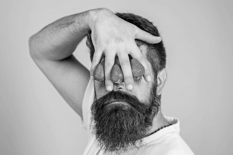 Stora truskawka Obsługuje brodatą modnisia chwyta rękę z truskawkami przed oczami Spojrzenie blokujący jagodami mężczyzna obrazy stock
