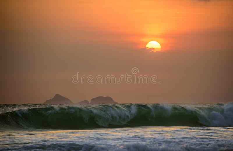Stora vågor av Atlantic Ocean på Ipanema sätter på land och den härliga solnedgången med moln och orange himmel, Rio de Janeiro arkivfoto