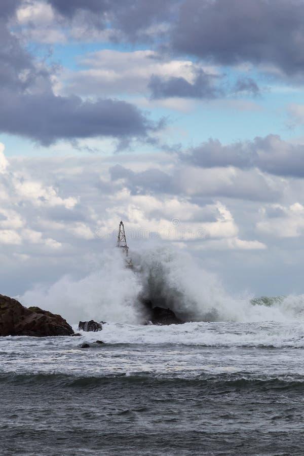 Stora vågor som kraschar in i fyren royaltyfri foto