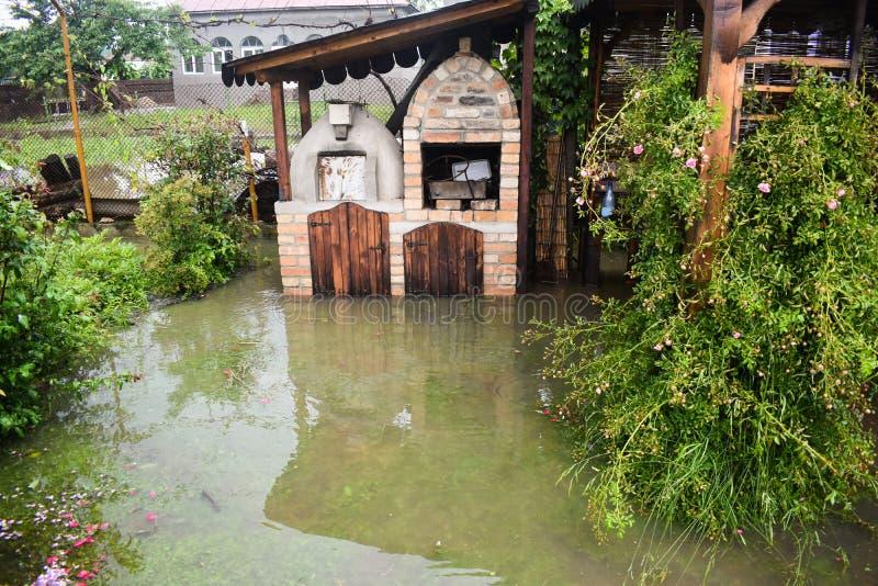 Stora vattenfloder efter massivt stormregn Trädgården och växterna täckas med smutsigt vatten Många skador efter skurkrollen arkivfoto