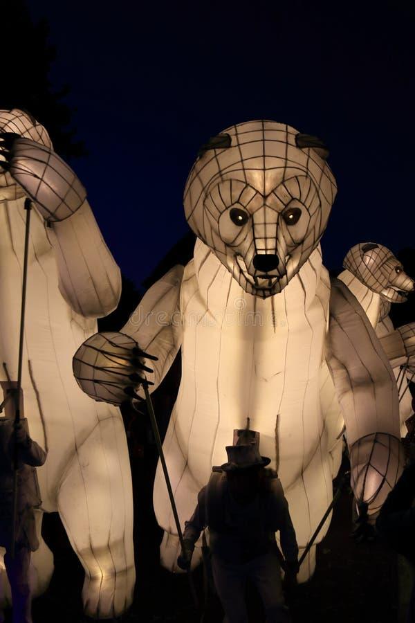 Stora vita artificiella isbjörnar på gatan nattetid arkivbild
