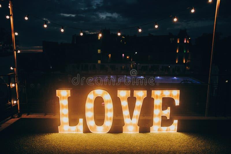 Stora vita förälskelsebokstäver i ljusa kulor för fotobås på bröllop royaltyfri fotografi