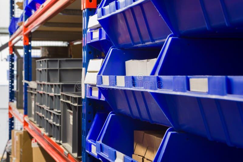 Warehouse Storage Bins and Racks. Storage bins and industrial storage racks in a warehouse shot with shallow focus stock images