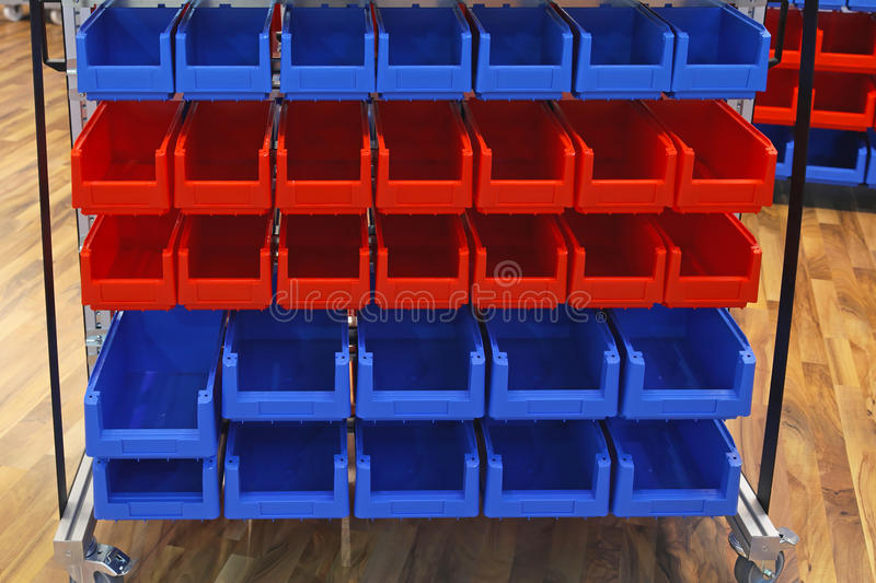 Storage bins. Red and blue plastic bins at sorting shelf in warehouse royalty free stock photo