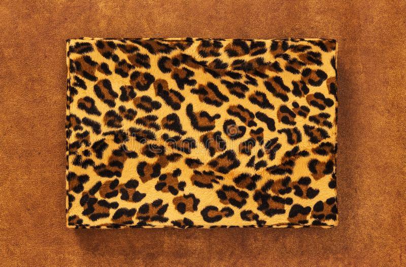 Storage box with leopard print on leather background. Storage box with vintage leopard print, on brown leather background stock image