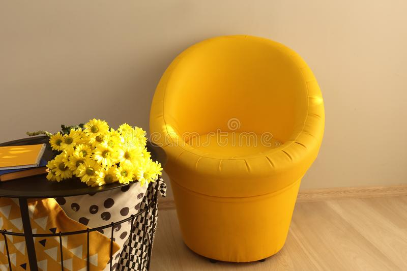 Storage table with beautiful flowers and cozy armchair in room stock photography