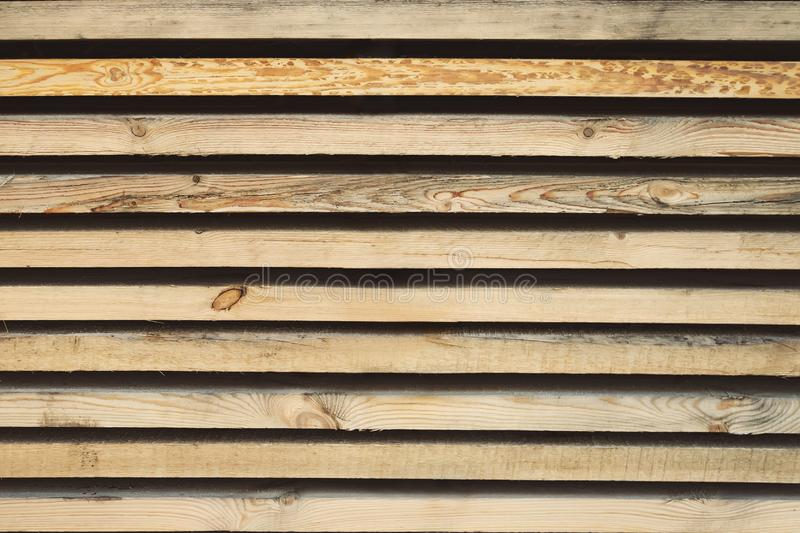 Storage timber. Lumber yard. Stock of timber wood construction in warehouse.Planks of wood stacked neatly on the shelves in the ha stock image