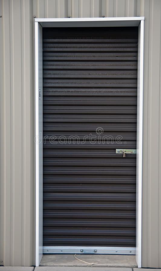 Storage Unit. Brown metal door with padlock, of an outdoor storage unit stock photo