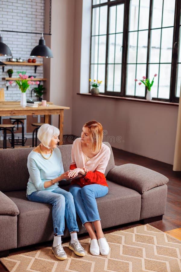 Storartad kvinnlig visande förlovningsring till farmodern som sitter på soffan royaltyfria foton