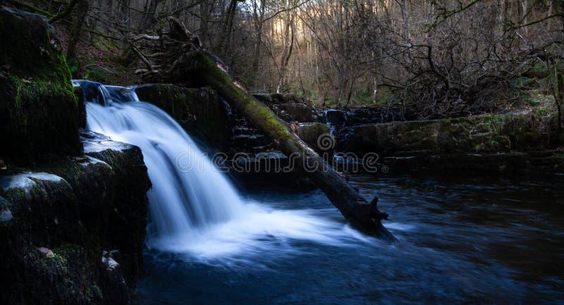Storartad lång exponering av en vattenfall i Brecon leder nationalparken på solnedgången royaltyfri foto