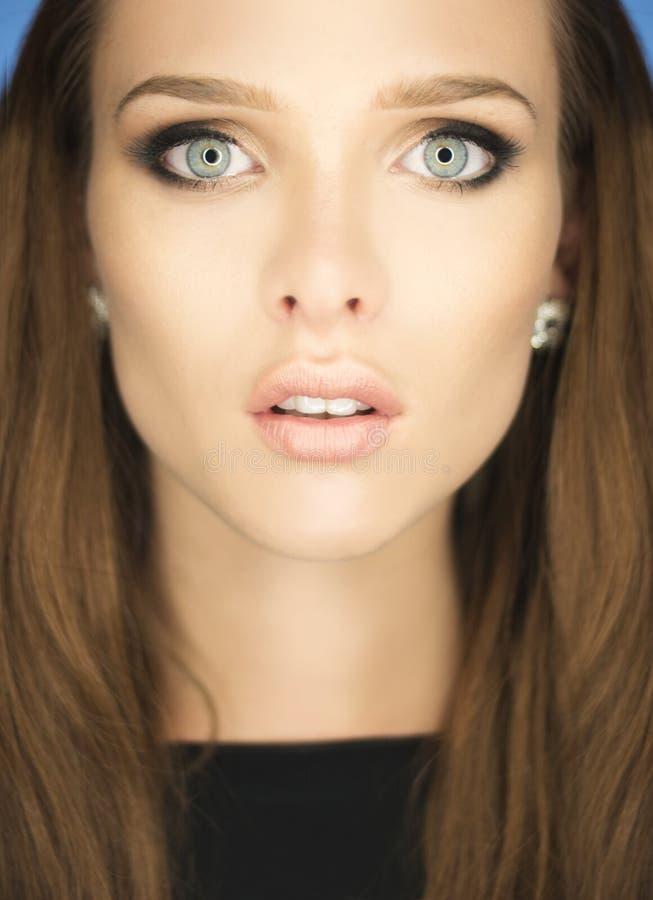 Storartad stående av en härlig ung kvinna med blåa ögon arkivbild
