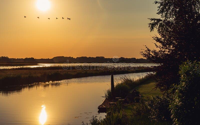 Storartat bygdlandskap vid vattnet för solnedgång arkivfoton