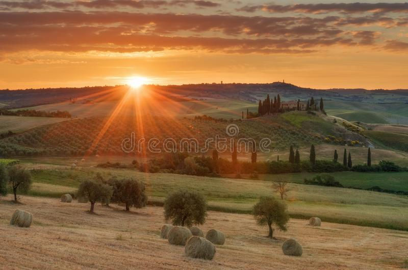 Storartat vårlandskap på soluppgång Härlig sikt av det typiska tuscan lantgårdhuset, kullar för grön våg royaltyfri fotografi