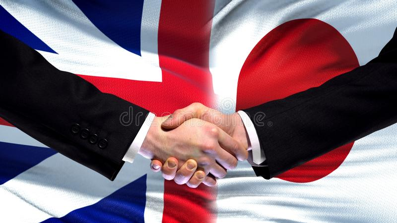 Storbritannien och Japan handskakning, internationellt kamratskap, flaggabakgrund arkivfoto