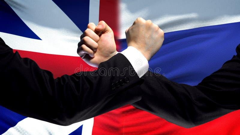 Storbritannien vs Ryssland konfrontation, nävar på flaggabakgrund, diplomati fotografering för bildbyråer