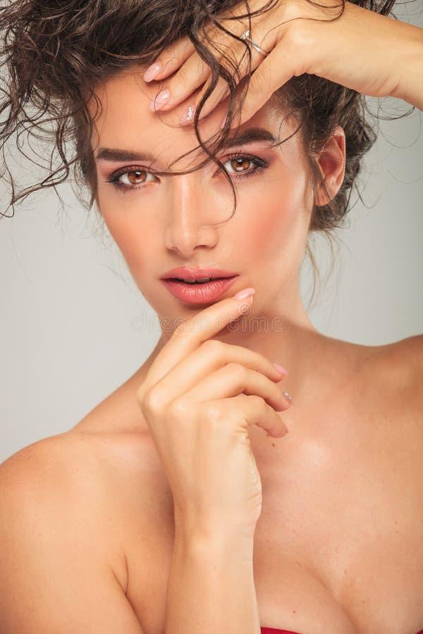 Storbystad modell som trycker på hennes framsida, medan fixa lockigt hår arkivfoton