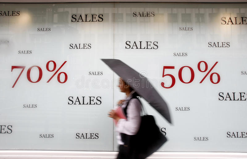 Store advertising sales. Store window advertising sales as a woman passes by carrying an umbrella