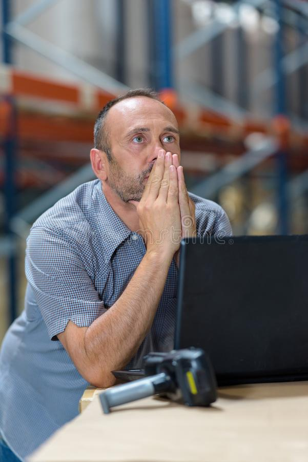 Store incharge using laptop in warehouse. Store incharge using a laptop in a warehouse stock image