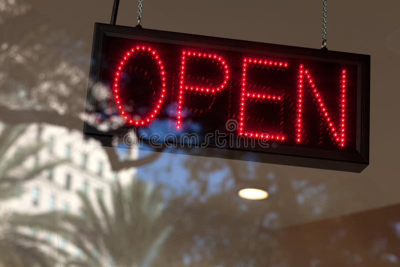 Store Open Sign. With window reflections of a downtown scene with trees, building, and blue sky in the background stock photos
