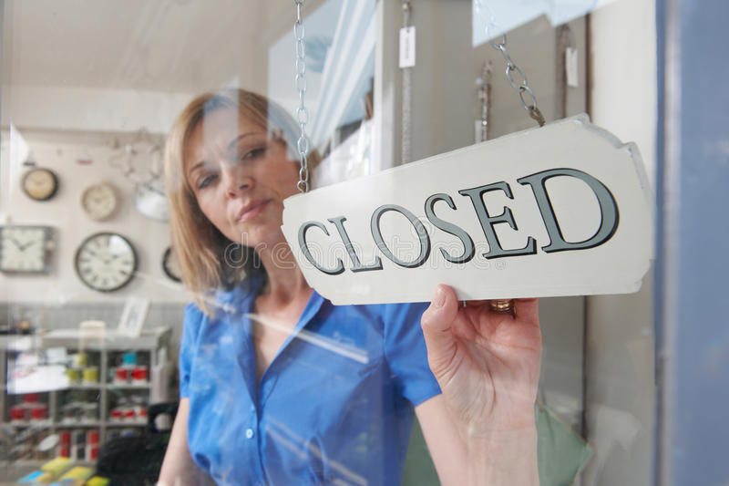 Store Owner Turning Closed Sign In Shop Doorway. Store Owner Turns Closed Sign In Shop Doorway royalty free stock photos