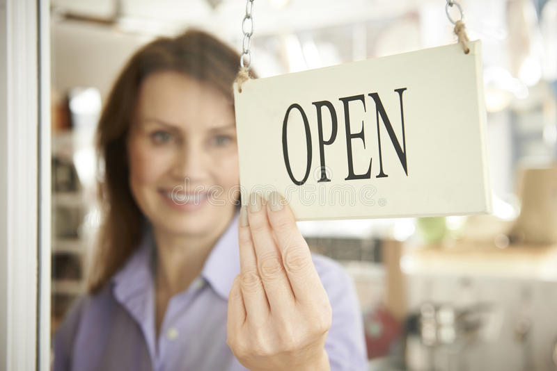 Store Owner Turning Open Sign In Shop Doorway. Female Store Owner Turning Open Sign In Shop Doorway stock photography