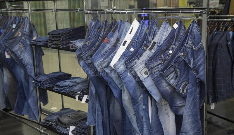 Store warehouse, men and women , unisex jeans denim pants , a lot of jeans pants, sale royalty free stock image