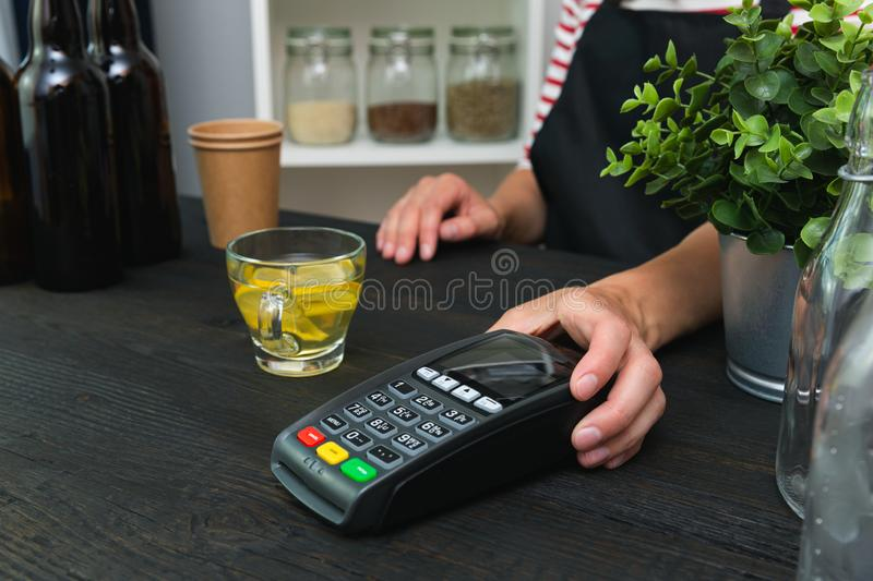 Store worker requesting for payment over nfc technology. Store worker holding pos terminal stock images