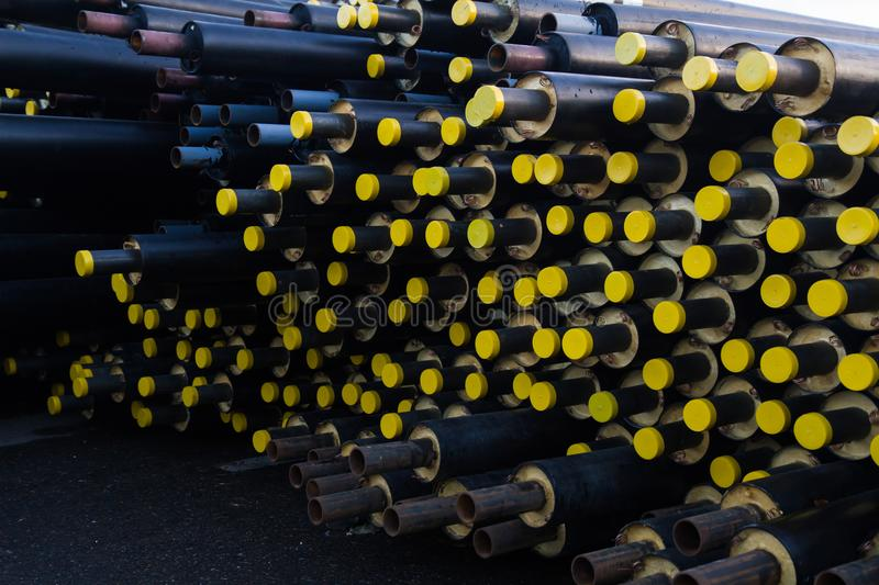 Stored many black steel pipe with heat insulation on construction site in a plastic tube wrapper lying with yellow lids pipes royalty free stock photography