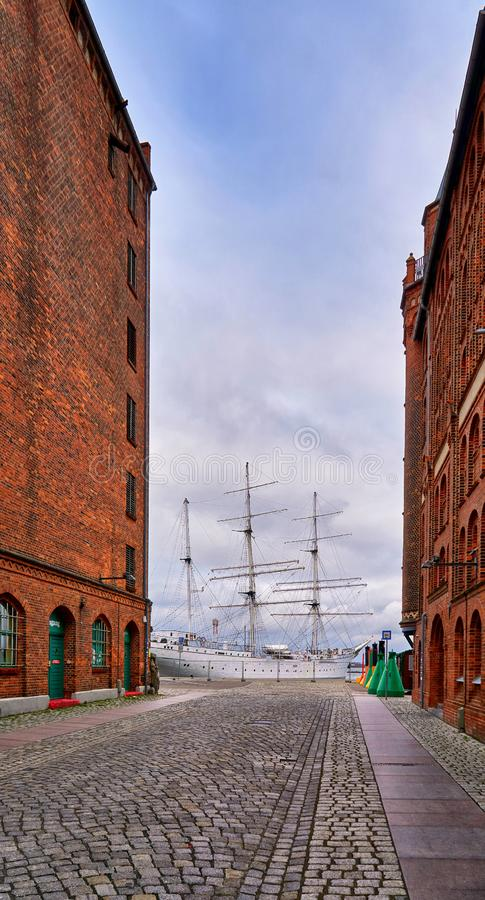 Storehouse in the Stralsund old town overlooking a large sailing ship in the harbor stock image