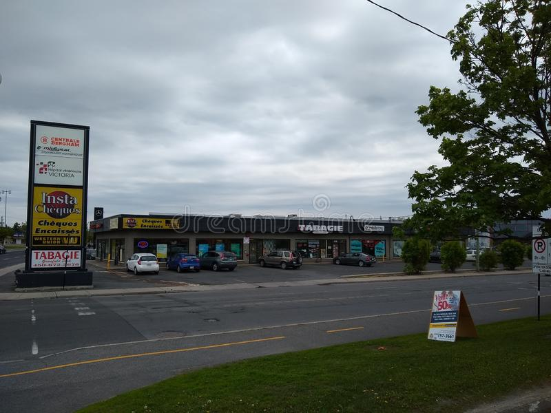 Stores viewed from across the street in Greenfield Park, Longueuil, Quebec, Canada. Longueuil, Quebec / Canada - June 1, 2019: Stores with several cars parked in royalty free stock images