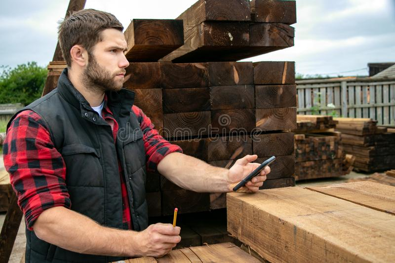 Lumber yard worker, carpenter at wood yard counts inventory with mobile device royalty free stock photography