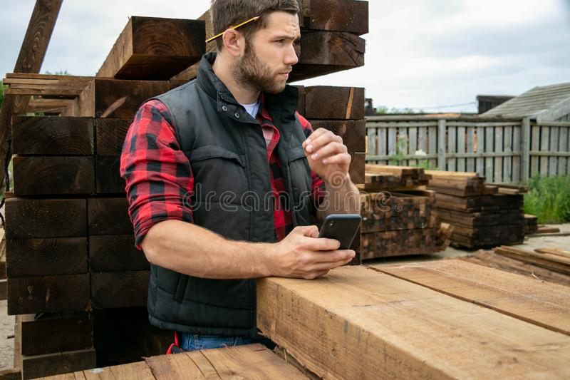 Lumber yard worker, carpenter at wood yard counts inventory with mobile device. Storesman at small business lumber yard counts stock and records it with his royalty free stock photography
