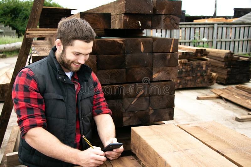 Lumber yard worker, carpenter at wood yard counts inventory with mobile device. Storesman at small business lumber yard counts stock and records it with his stock photos