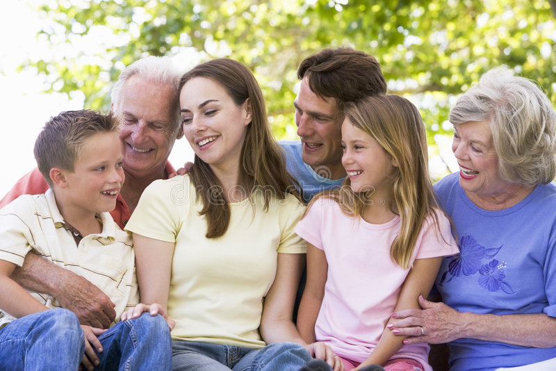 storfamilj som ler utomhus royaltyfria bilder
