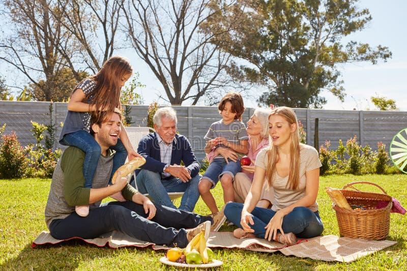 Storfamiljen har picknicken eller partiet i trädgården fotografering för bildbyråer