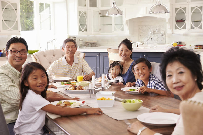 Storfamiljgrupp som hemma äter mål tillsammans royaltyfria foton