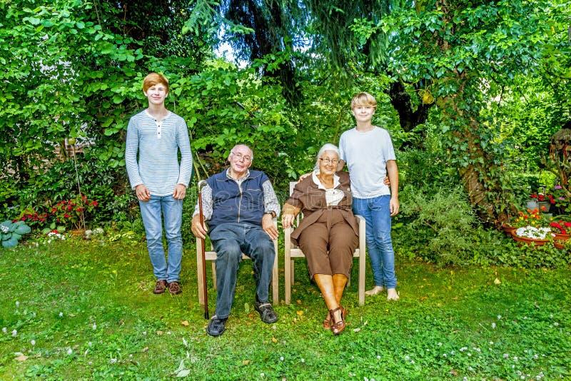 Storfamiljgrupp som poserar i trädgården royaltyfri foto