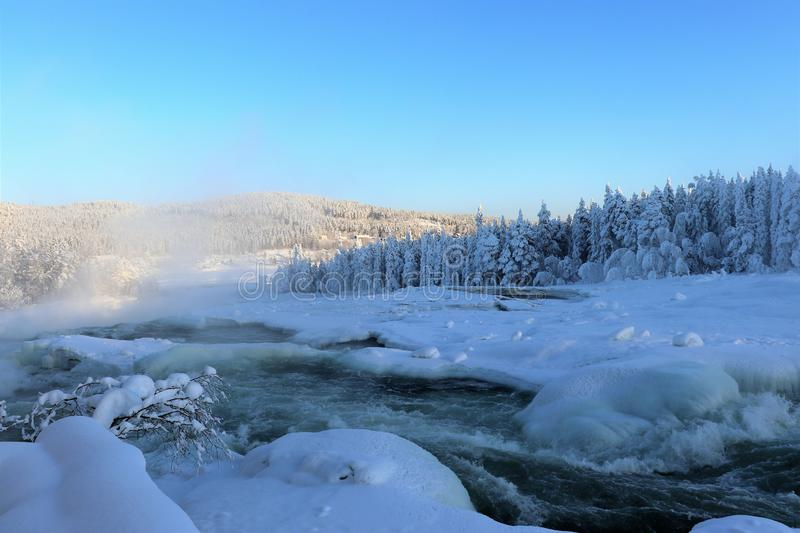 Storforsen in a fabulous winter landscape. Storforsen is Europe`s largest unregulated rapids, where the total length of the entire rapids, from start to finish stock photo