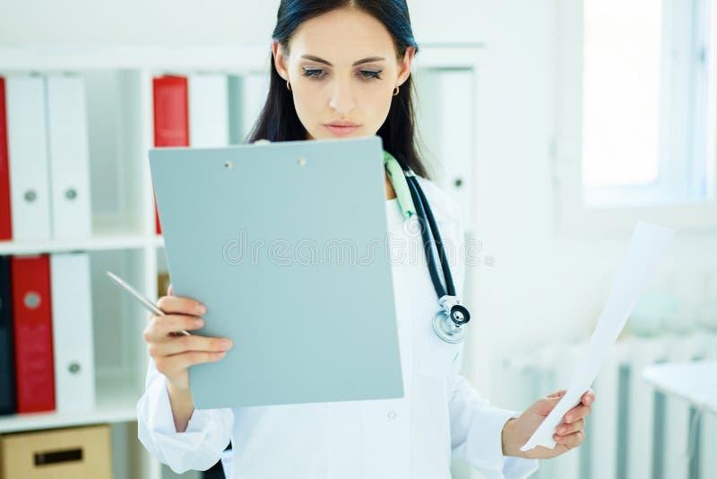 Storia del paziente femminile del cuscinetto e della lettura del ritaglio della tenuta di medico fotografie stock